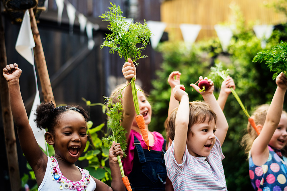 Photo of children holding up vegetables